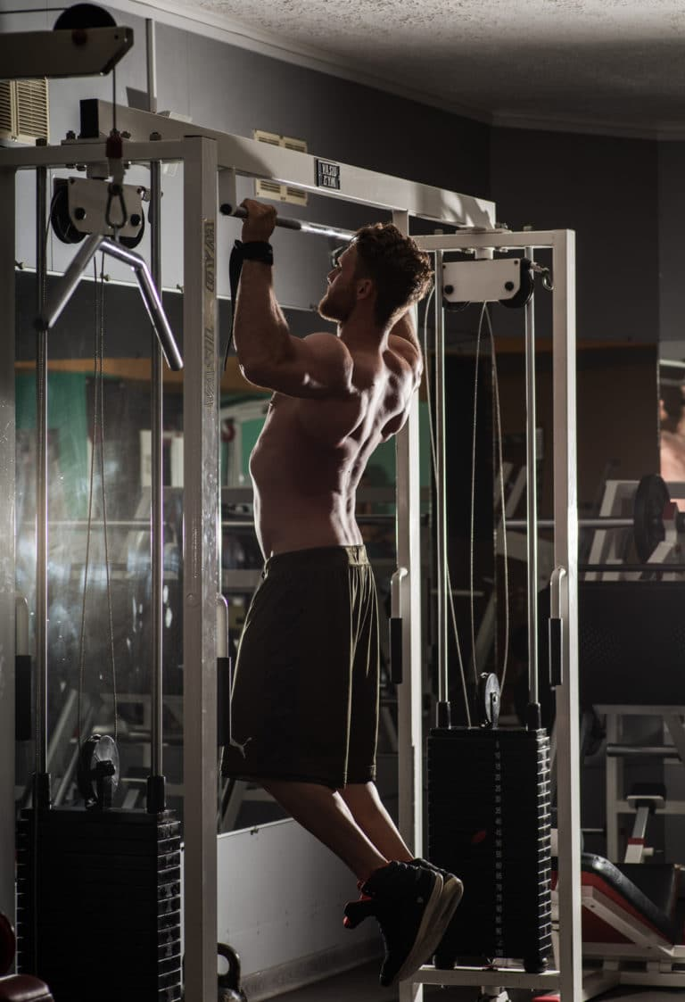 Strong sportsman performing pull ups in gym